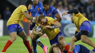 Romania's Csaba Gal is tackled for the ball during the Rugby World Cup Pool D match between France and Romania at the Olympic Stadium, London, Wednesday, Sept. 23, 2015. (AP Photo/Kirsty Wigglesworth)